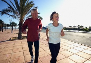 Mature Couple Jogging Together on Promenade
